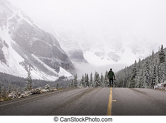 Photographer walks down a road in the winter with his camera...