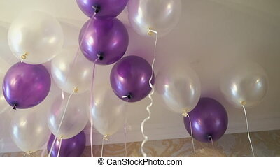 White and purple balloons floating on the ceiling