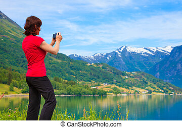 Tourist taking photo at norwegian fjord - Tourism and travel...