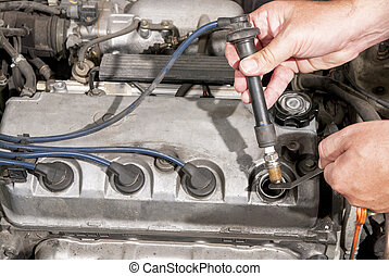 Mechanic tests a spark plug in an automobile - Checking a...