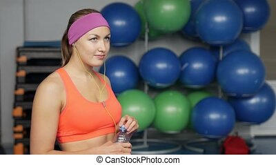 Beautiful fitness athlete woman resting drinking water after...