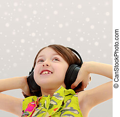 Little girl listening to music headphones. - Closeup...
