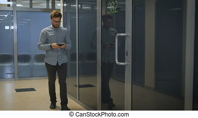 Young entrepreneur walks in corridor with tablet smart phone...