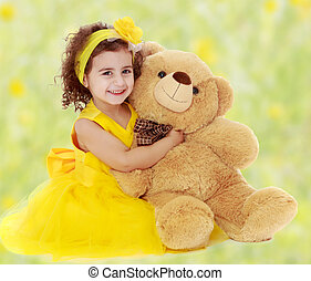 Little girl hugging Teddy bear - Joyful little girl in a...