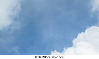 Aircraft trail between two clouds