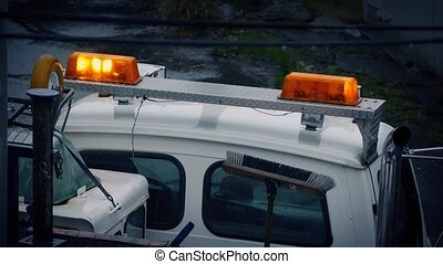 Lights Flashing On Vehicle In Rain - Maintenance truck with...