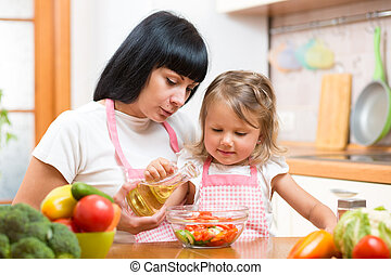 Mother teaching child daughter making salad in kitchen. Cooking concept of happy family preparing food for dinner.
