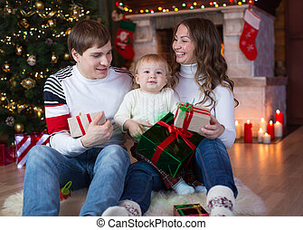 Family exchanging gifts in front of Christmas tree - Family...