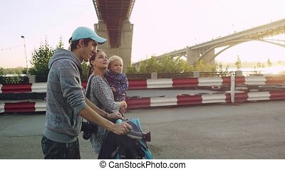 Young happy family with a little son walking together in autumn promenade during sunset in slowmotion. 1920x1080