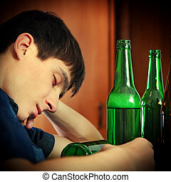 Young Man sleep with a Beer - Toned Photo of Tired Young Man...
