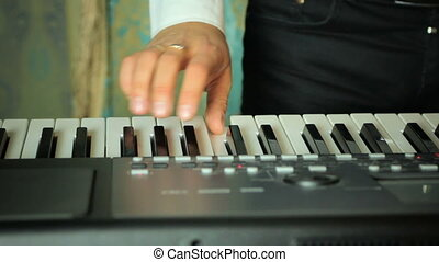 Man playing on a synthesizer - A man playing on a...