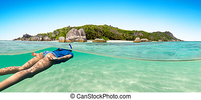Young woman snorkling next to tropical island in shallow...