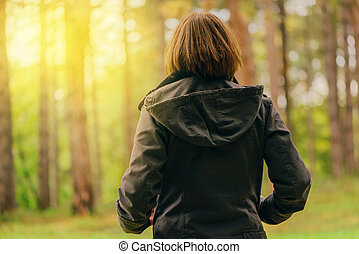 Rear view of casual female looking at sunlight through trees
