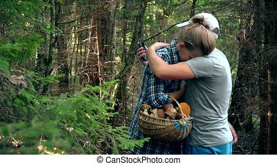 Man hug sad woman because of loss in forest when picking mushrooms