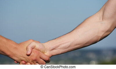 Friendly handshake of two unrecognizable muscular white men...