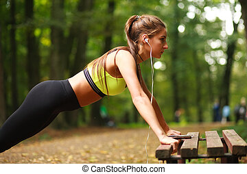 Woman with headphones doing push-ups exercises in park -...