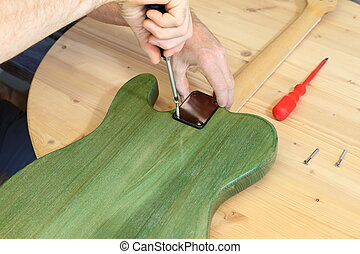building a green electrical guitar - worker is building a...