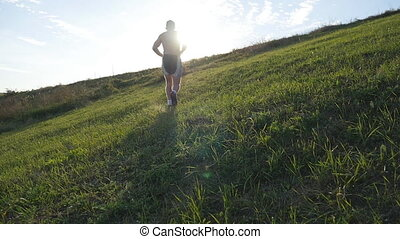 Young man running over green hill over blue sky background....