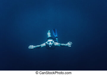 Free diver swimming underwater - Sporty young man free diver...