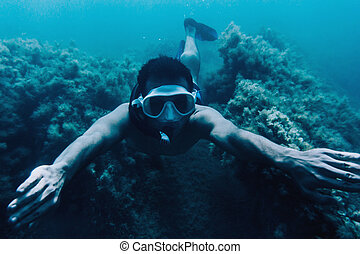 Man snorkeling among seaweed - Underwater image of young man...