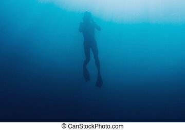 Underwater silhouette of freediver - Silhouette of young man...