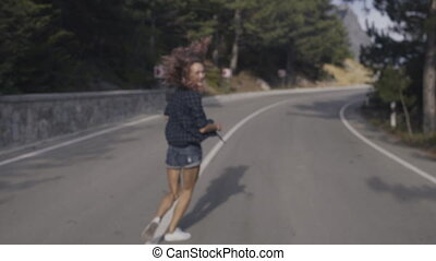Happy girl with curly hair running down the road in slow...
