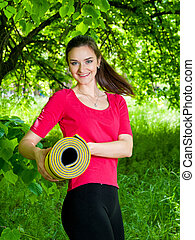 Woman on her way to yoga class - the girl with the sport mat...