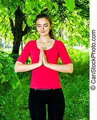 Girl meditating in park - beautiful girl are meditates in...
