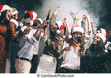 New Year party. Group of beautiful young people in Santa hats throwing colorful confetti and looking happy