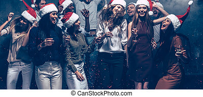 Enjoying New Year party. Group of beautiful young people in Santa hats dancing and looking happy