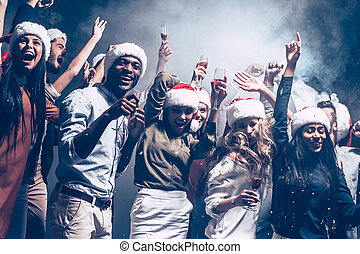 New Year party with best friends. Group of beautiful young people in Santa hats dancing and looking happy