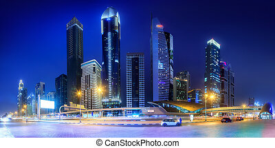 Panoramic view of metro station and road in Financial district at night, Dubai, UAE