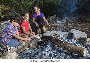 three kids in a campfire in a mediterranean forest