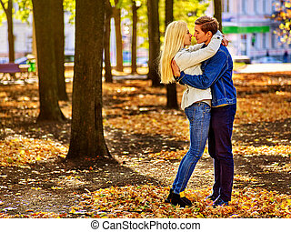 Young couple hugging and flirting in park. Autumn love. -...