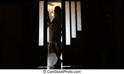 silhouette of young woman in a doorway. Blur pose.