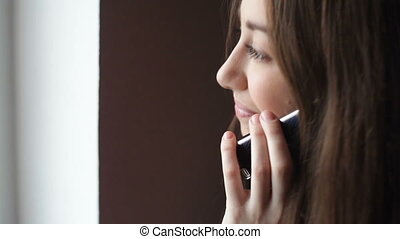 young businesswoman talking on mobile phone on office...