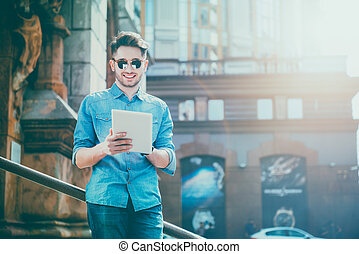 DElighted smiling young man using tablet - Full of positive...