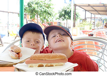 Two children with hotdogs at a restaurant