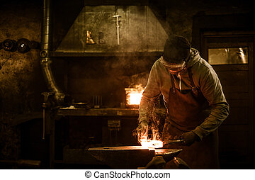 Blacksmith with brush handles the molten metal on the anvil...