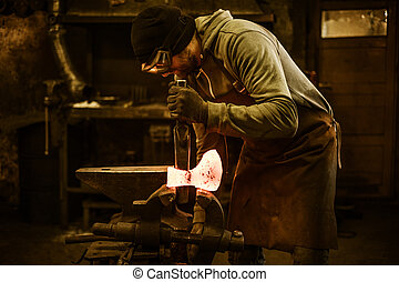 Blacksmith forging the molten metal on the rusty vise in...