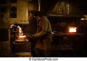 Blacksmith forging the molten metal on the power hammer in...