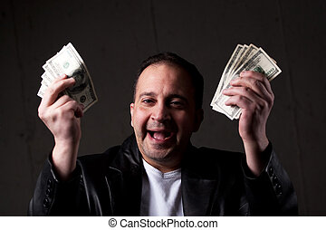 Man Holding Out Money - A man celebrating holding handfuls...