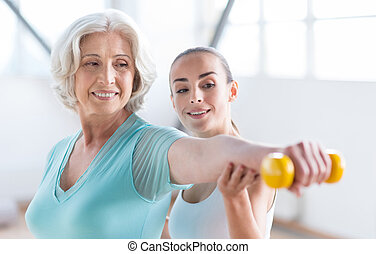 Optimistic cheerful woman exercising with a coach