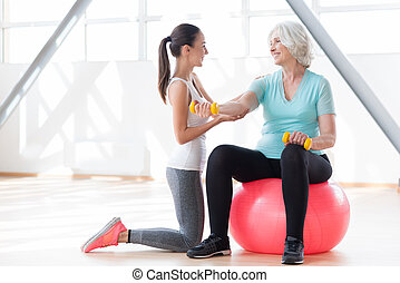 Joyful female coach working out with an elderly woman