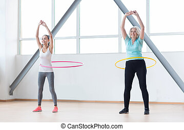 Persistent positive women exercising with hula hoops -...
