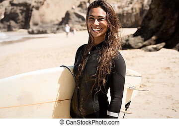 Girl standing on the beach holding a surfboard. water sport