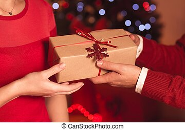 Giving Christmas present wrapped in brown paper