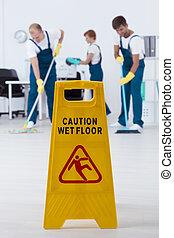 Wet floor sign - Shot of yellow wet floor sign and cleaners...