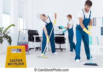 Cleaners mopping floor - Two cleaners mopping floor and...
