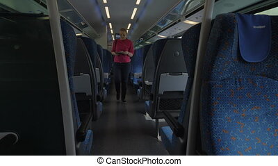Shot of young blond woman going along train and searching...